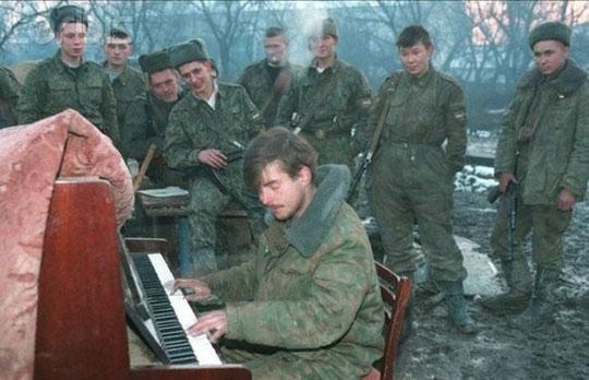 Soldado a tocar piano enquanto outros soldados assistem