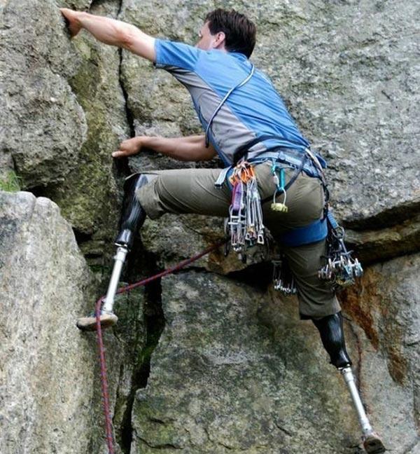 Homem com próteses escalando uma montanha