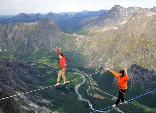 Duas pessoas andando sobre uma corda, a uma grande altitude