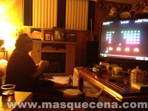Homem sentado a jogar numa consola de jogos